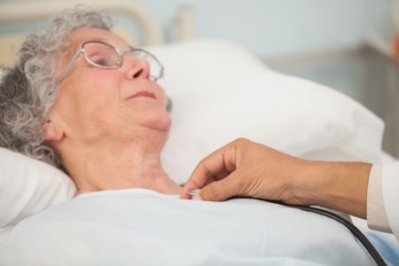 lying on bed: Doctor using stethoscope on elderly female patient in hospital bed Stock Photo