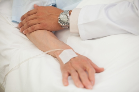 Doctor touching arm of elderly lady in hospital bed photo