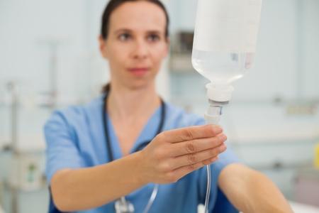 female catheter: Nurse adjusting drip in hospital room