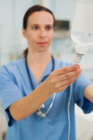 female catheter: Nurse connecting an intravenous drip in hospital room