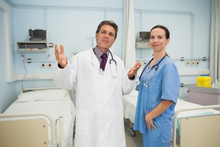 Happy doctor and nurse in hospital room photo