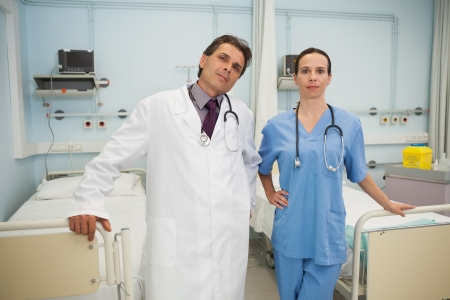 tend: Doctor and nurse smiling in hospital bedroom Stock Photo