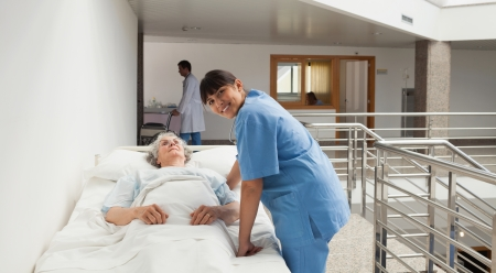 hospital corridor: Nurse smiling next to an elderly lady in hospital bed in corridor Stock Photo