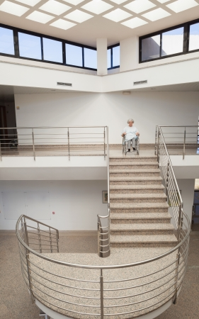 Elderly lady in wheelchair at top of stairwell in hospital photo