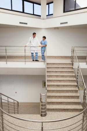 Nurse and doctor talking at top of hospital stairwell Stock Photo - 15585052