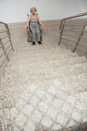 uneasiness: Anciana en silla de ruedas pegado en la parte inferior de las escaleras del hospital con los brazos abiertos Foto de archivo