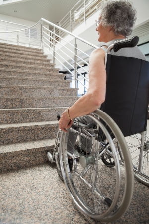 solicitous: Elderly lady in wheelchair looking up hospital stairs Stock Photo