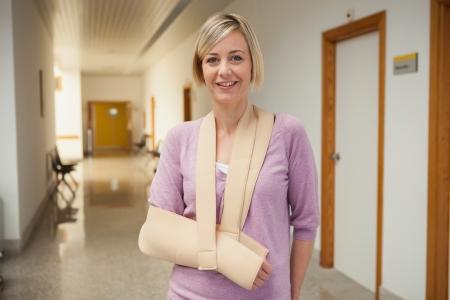 brazo roto: Paciente con fractura de brazo en cabestrillo en pasillo del hospital