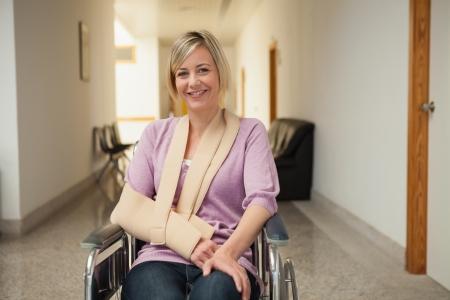 paraplegico: Paciente en silla de ruedas con el brazo en cabestrillo en pasillo del hospital Foto de archivo