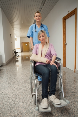 Nurse puching wheelchair of patient with arm sling in hospital corridor photo