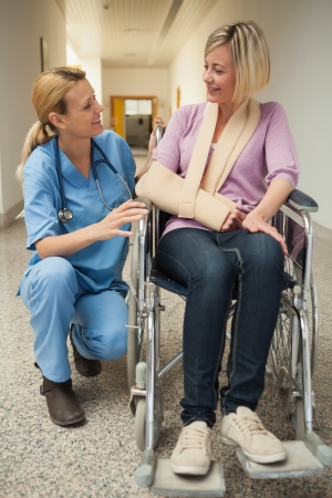 paraplegico: Enfermera hablando con el paciente en silla de ruedas con el brazo en cabestrillo en el pasillo del hospital Foto de archivo