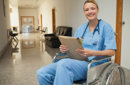 Smiling nurse in a wheelchair holding a folder in hospital corridor photo