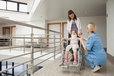 Nurse talking with child in wheelchair and neck brace with mother in hospital corridor photo