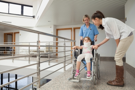 Nurse pushing child with neckbrace in wheelchair with mother in hospital corridor photo