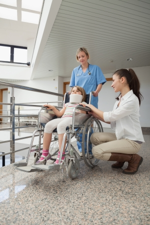 crouches: Mother crouches next to her child in wheelchair with nurse pushing it in hospital corridor