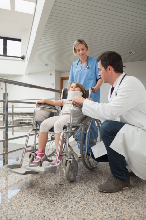 Doctor crouching next to child in wheelchair with neck brace with nurse pushing it photo