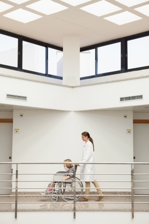 Female doctor pushing child with neckbrace in wheelchair in hospital corridor Stock Photo - 15590071