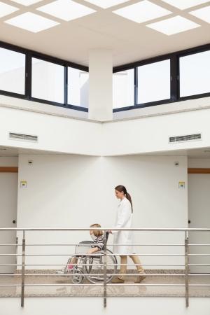Female doctor pushing child with neckbrace in wheelchair in hospital corridor Stock Photo - 15590071