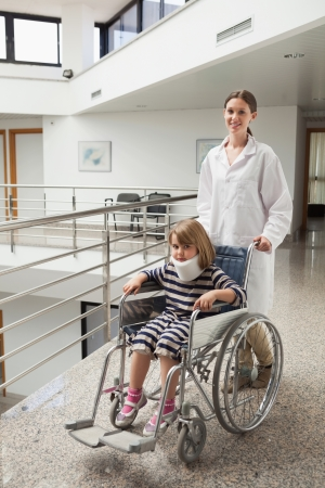 Child in neck brace being pushed in wheelchair by doctor in hospital corridor Stock Photo - 15592701