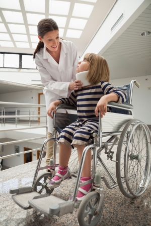Doctor talking to chld with neck brace in wheelchair in hospital corridor Stock Photo - 15592932