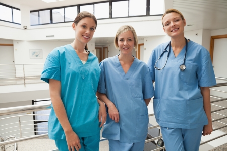 stairwell: Three smiling nurses leaning against railing at hospital stairwell Stock Photo
