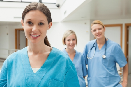 Smiling nurse with two nurse friends in hospital corridor photo