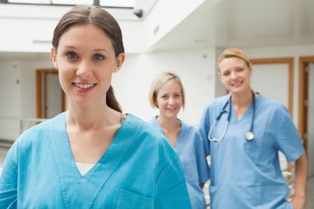 enfermera: Sonriente enfermera con dos amigos de enfermer�a en pasillo del hospital