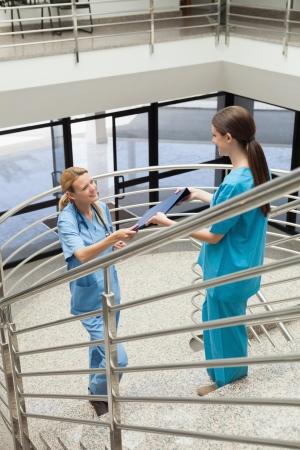 Nurse handing folder to other nurse on stairwell photo