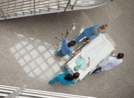Three nurses and one doctor pushing a patient in a gurney in hospital corridor photo