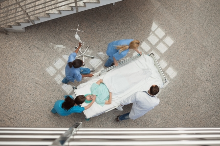 Three nurses and one doctor pushing one patient in a bed in hospital corridor photo