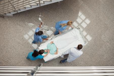 paciente en camilla: Tres enfermeras y un m�dico con s�lo pulsar un paciente en una cama en el pasillo del hospital