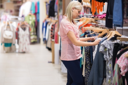 Woman is standing in a shop looking at clothes on a rail photo