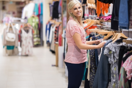 Woman is smiling by the clothes rail in a clothes shop Stock Photo - 15592919