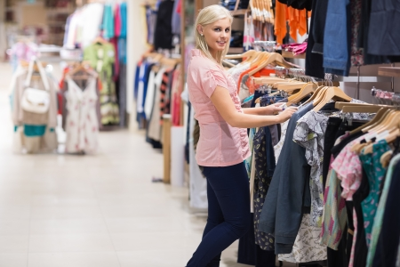 Woman is standing in a shop searching for clothes photo