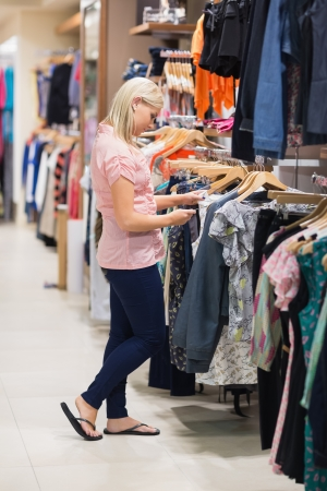 Woman standing in a shop searching for clothes Stock Photo - 15593002