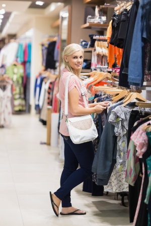 clothes rail: Woman standing in a shop looking at the camera smiling searching for clothes Stock Photo