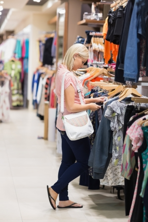 Woman standing in a shop looking at clothes photo