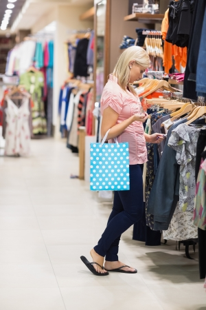 Woman is searching for clothes while holding a bag Stock Photo - 15592587