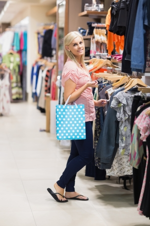Woman at a shopping mall holding a bag smiling  Stock Photo - 15592746