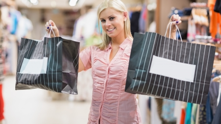 Woman is standing in a shop holding two bags Stock Photo - 15592570