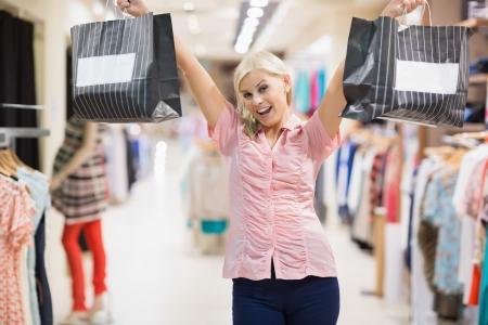 Woman stretching arms in the air holding two bags Stock Photo - 15592836