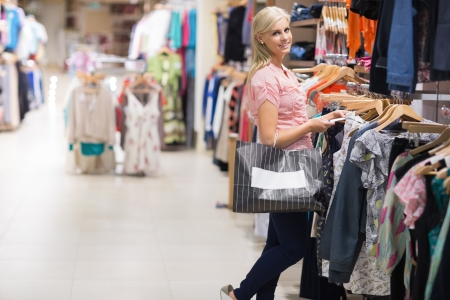 Woman standing in a shop holding bags smiling  photo