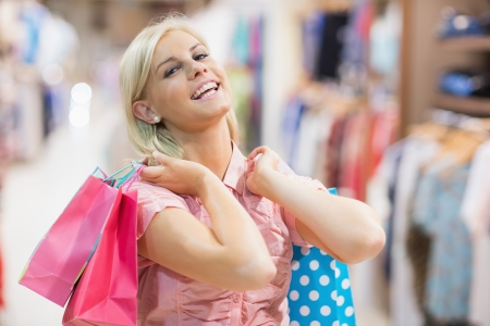 Woman holding bags in her hands smiling in a shop Stock Photo - 15592869