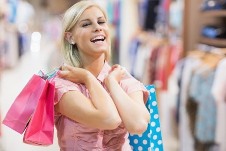 Woman holding two bags laughing in clothes shop photo