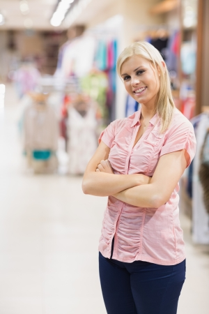Woman standing in a shop smiling arms crossed Stock Photo - 15591975