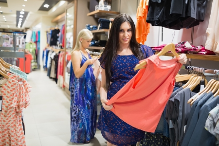 Woman is standing in a shop holding clothes Stock Photo - 15585064