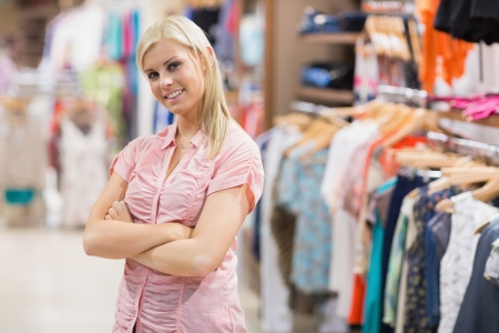 clothes rail: Woman standing in shop smiling with arms crossed Stock Photo