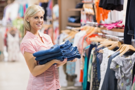 Woman standing in a shop holding jeans  photo