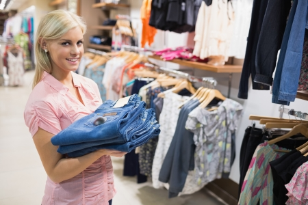 Woman standing in a shopping mall holding pants in her hands Stock Photo - 15593314