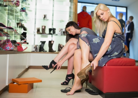 Women sitting trying on shoes Stock Photo - 15592047
